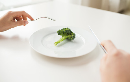 woman knife: healthy lifestyle, diet, vegetarian food and people concept - close up of woman with fork and knife eating broccoli