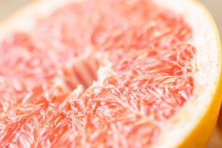 juicy: healthy eating, food, fruits and diet concept - close up of fresh juicy grapefruit slice