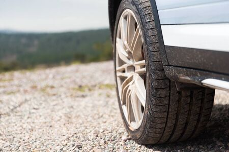 dirty car: transport, driving and motor vehicle concept - close up of dirty car wheel on cliff Stock Photo