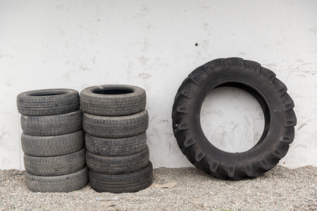 utilized: tire, maintenance, service and motor transport concept - close up of wheel tyres stored near wall