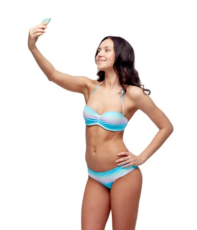 young girl bikini: people, technology, summer and beach concept - happy young woman in bikini swimsuit taking selfie with smatphone