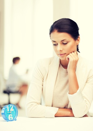 career timing: business and time management concept - businesswoman looking at alarm clock