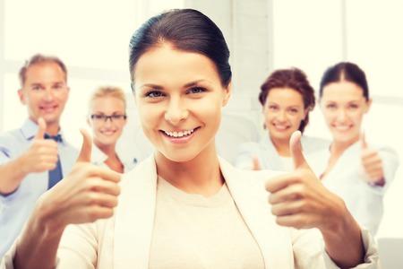 Erfolg: Business und Erfolg - glücklich Geschäftsfrau zeigt Daumen nach oben im Büro Lizenzfreie Bilder