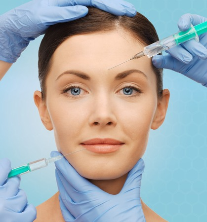 dermal: plastic surgery, injections and beauty concept - beautiful young woman face and surgeon hands with syringes over blue background