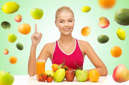 健康的な食事、ダイエット、デトックス、人々 コンセプト - 有機食品や果物の立ち下がりの果物と緑の背景の上に指を上向きに幸せな若い女 写真素材