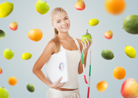 mujer alegre: la alimentación, la dieta, el control de peso saludable y el concepto de la gente - mujer joven feliz con la escala, manzana verde y cinta métrica sobre fondo gris con la caída de las frutas