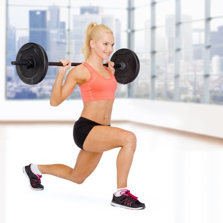 lifting: fitness, sport, weightlifting and people concept - sporty woman exercising with barbell over gym background Stock Photo