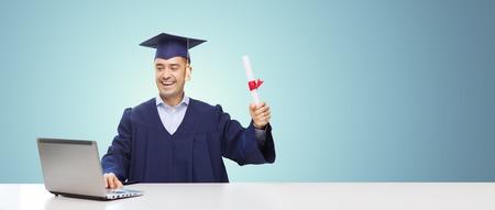GRADUADO: educación, graduación, negocio, tecnología y concepto de la gente - estudiante feliz adulta en birrete con el diploma y el ordenador portátil sentado en la mesa sobre fondo azul Foto de archivo