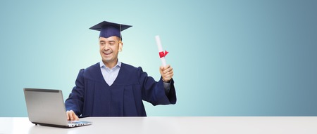 education, graduation, business, technology and people concept - happy adult student in mortarboard with diploma and laptop computer sitting at table over blue background