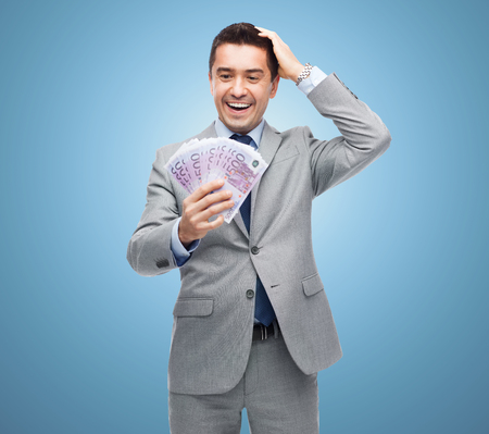 eur: business, people and finances concept - happy laughing businessman with euro money over blue background