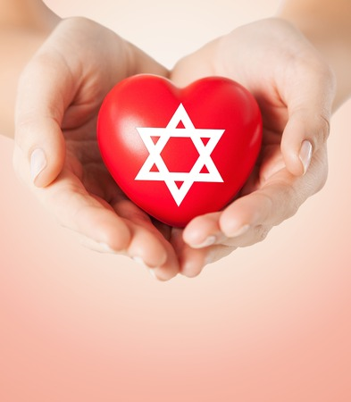 jews: religion, christianity, jewish community and charity concept - close up of female hands holding red heart with star of david symbol over beige background