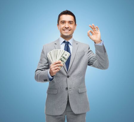 money exchange: business, people and finances concept - smiling businessman with american dollar money over blue background