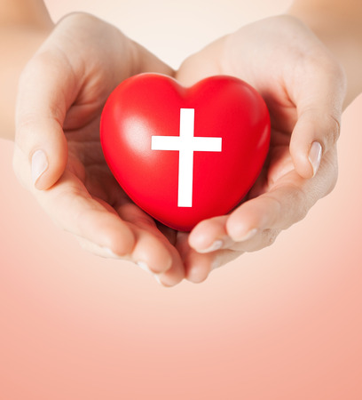 christian community: religion, christianity and charity concept - close up of female hands holding red heart with christian cross symbol over beige background