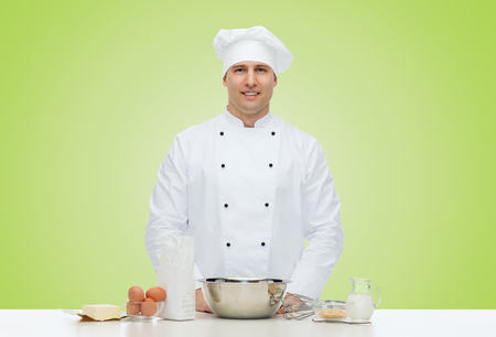 cook: cooking, profession, haute cuisine, food and people concept - happy male chef cook baking over green background