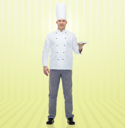 empty of people: cooking, profession, advertisement and people concept - happy male chef cook showing something on empty plate over yellow background