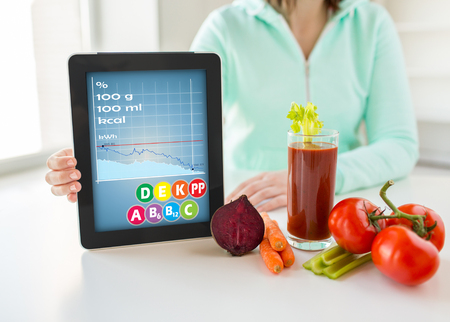 eating up: healthy eating, technology, diet and people concept - close up of woman hands holding tablet pc computer with calories and vitamins chart, vegetables Stock Photo
