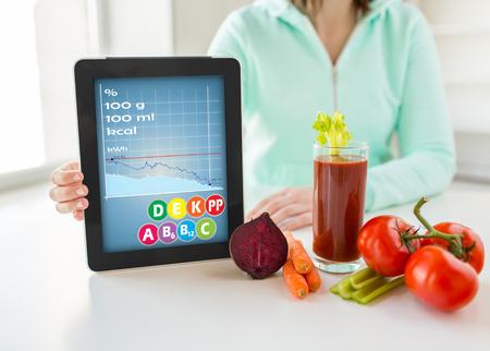 dieta sana: la alimentación saludable, la tecnología, la dieta y el concepto de la gente - cerca de manos de la mujer que sostienen la tablilla del ordenador PC con calorías y tabla de vitaminas, verduras Foto de archivo