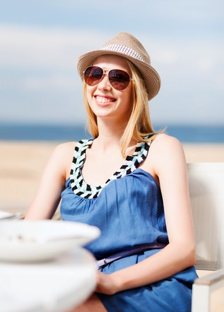 tanned girl: summer holidays and vacation - girl in shades in cafe on the beach