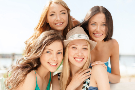 niñas sonriendo: summer holidays and vacation concept - group of smiling girls in cafe on the beach