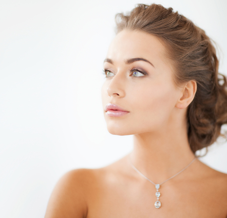 close up of beautiful woman wearing shiny diamond necklace Stock Photo