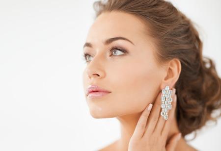 光沢のあるダイヤモンドのイヤリングを着て美しい女性のクローズ アップ