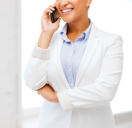 chatting: business, and communication concept - smiling african businesswoman with smartphone in office