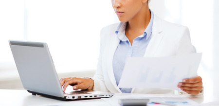 tax forms: business and tax concept - african businesswoman working with computer in office