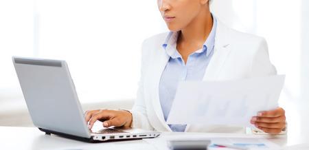 negócio e do conceito de imposto - mulher de negócios africano que trabalha com o computador no escritório