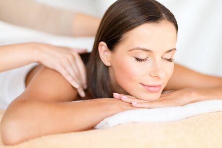 nice body: health, beauty, resort and relaxation concept - beautiful woman with closed eyes in spa salon getting massage