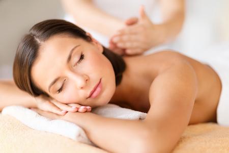 descansando: la salud, la belleza, la estaci�n y el concepto de relajaci�n - hermosa mujer con los ojos cerrados en sal�n del balneario que consigue masaje Foto de archivo