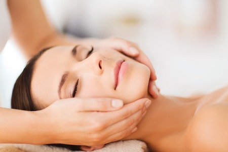 therapeutic massage: spa, resort, beauty and health concept - beautiful woman in spa salon getting face treatment