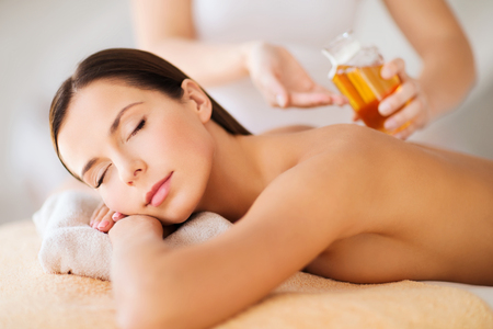 aromatherapy oils: beauty, spa, resort and relaxation concept - beautiful woman in spa salon