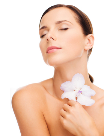 beauty and health: health and beauty concept - relaxed woman with orhid flower