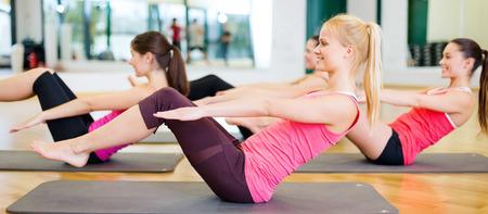 fitness, sport, trénink, posilovna a koncept životního stylu - skupina usmívající se ženy vykonávají na rohože v posilovně
