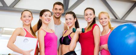 mujeres juntas: fitness, deporte, entrenamiento, gimnasio y estilo de vida concepto - grupo de gente sonriente en el gimnasio Foto de archivo