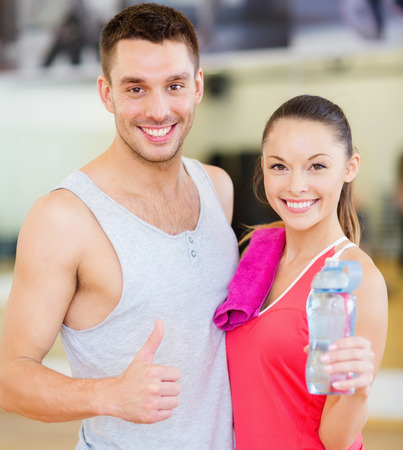 fitness gym: fitness, sport, training, gym and lifestyle concept - two smiling people in the gym
