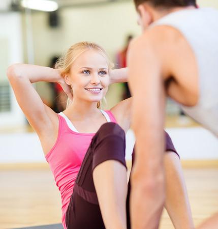 mujeres juntas: fitness, deporte, entrenamiento, gimnasio y estilo de vida concepto - entrenador varón con la mujer haciendo abdominales