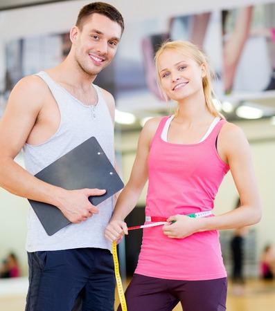 forme et sante: fitness, sport, formation, alimentation, salle de gym et style de vie concept - deux gens souriants avec presse-papiers et ruban à mesurer dans le gymnase Banque d'images