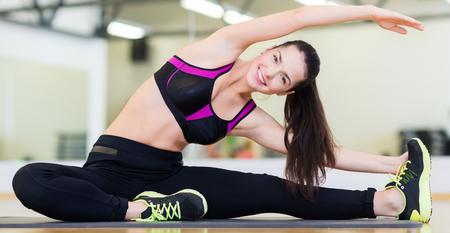 mujer alegre: fitness, deporte, entrenamiento, gimnasio y estilo de vida concepto - adolescente sonriente que estira en la estera en el gimnasio Foto de archivo