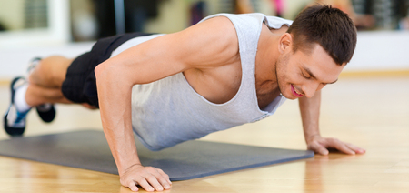 fitness, sport, training, gym and lifestyle concept - smiling man doing push-ups in the gym Stock Photo - 47304465