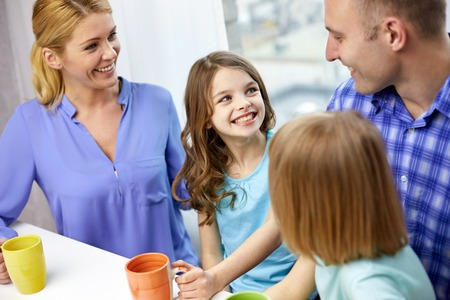parents love: family, childhood, breakfast and people - happy parents and children drinking tea with cups at home