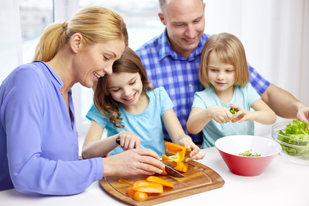 food, children, culinary and people concept - happy family with two kids cooking vegetables at home