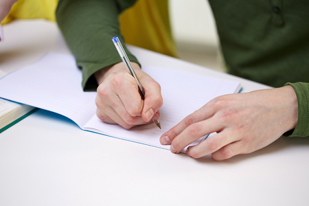 body writing: people and education concept - close up of male hands writing to notebook at school Stock Photo