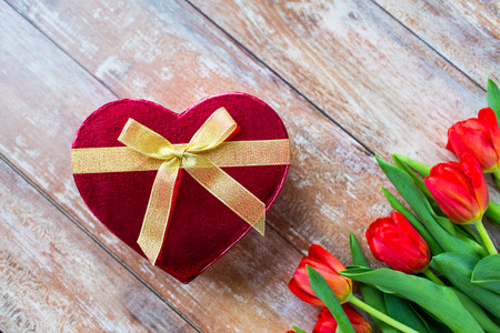 red box: flowers, valentines day and holidays concept - close up of red tulips and heart shaped chocolate box on wooden table Stock Photo