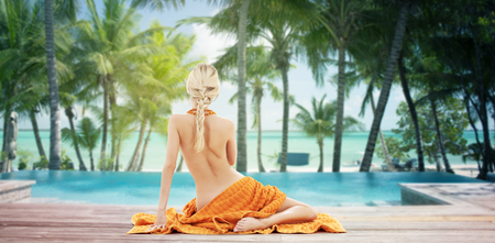 people, travel, tourism, summer and people concept - woman with orange towel from back over tropical beach with swimming pool background photo