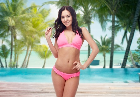 pink bikini: people, travel, tourism, summer and sexual concept - happy young woman posing in pink bikini swimsuit over swimming pool and beach with palm trees background Stock Photo
