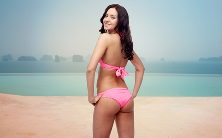 sexy pose: people, fashion, swimwear, summer and travel concept - happy young woman in pink bikini swimsuit looking back over resort swimming pool or beach Stock Photo