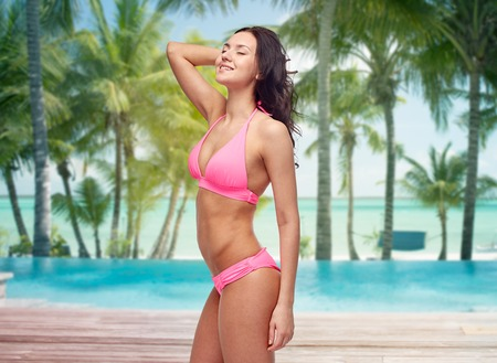 sexy young girl: people, travel, tourism and summer concept - happy young woman posing in pink bikini swimsuit over swimming pool and beach with palm trees background
