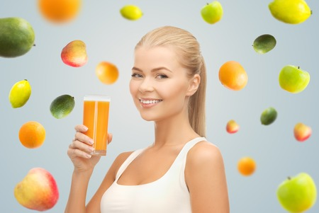 c to c: healthy eating, diet, detox and people concept - happy young woman holding glass of orange juice over gray background with falling fruits