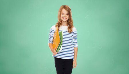 niños sonriendo: educación, las personas, niños y concepto de la escuela - chica feliz celebración de las carpetas de colores sobre fondo verde bordo